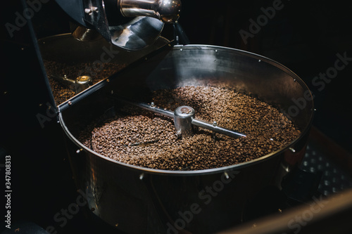 Shiny stainless large metal vat for roasting coffee beans close-up on dark background Canvas Print