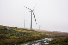 Three Large Wind Turbines In Scotland Against A Misy Background.