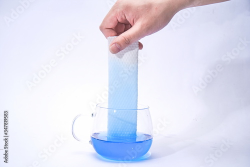 Photo Pick up a paper towel in one hand and place it in the blue test liquid to test i