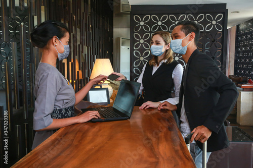 Couple and receptionist at counter in hotel wearing medical masks as precaution against virus Canvas Print