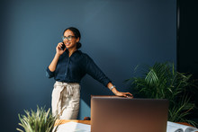 Happy Entrepreneur Leaning To A Chair And Looking Away While Talking On Mobile Phone