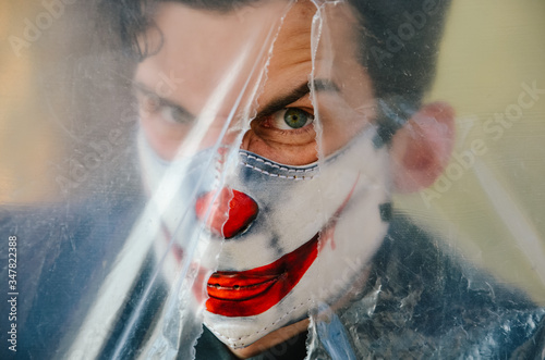 Angry guy in leather cosplay joker mask from virus look through oilcloth Canvas Print