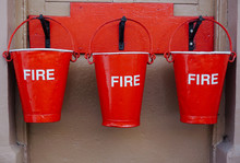 Close-up Of Red Fire Buckets Hanging Outdoors