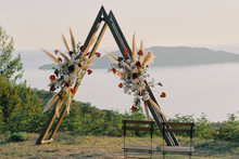 Original Wedding Arch On Top Of The Mountain With White And Red Flowers At Sunset. Romantic Ceremony In The Style Of Boho