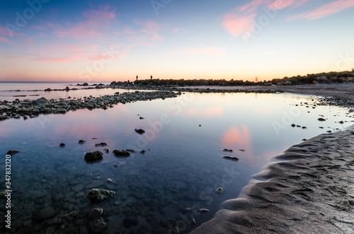 Il mare calmo di Ostia riflette il cielo con le nuvole rosa mentre delle persone Canvas-taulu