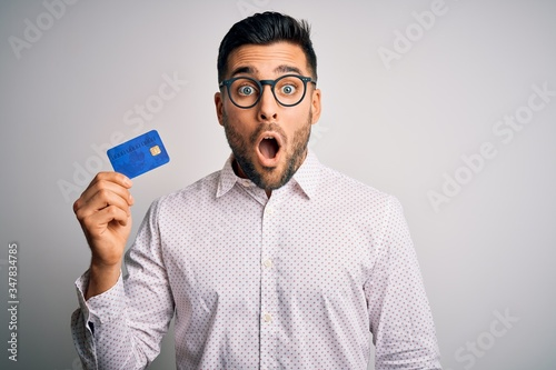 Fototapeta Young business man holding credit card over isolated background scared in shock with a surprise face, afraid and excited with fear expression obraz