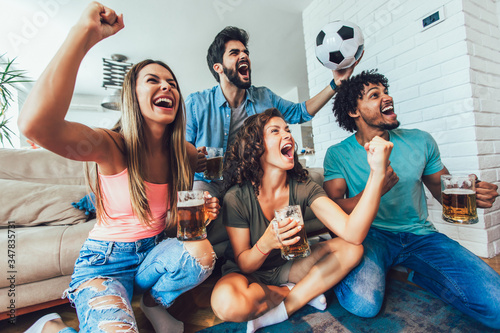 Very excited friends having fun by watching football match and eating at home, indoors Fototapet