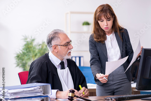 Old male judge and his young secretary in the office Canvas