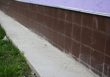 Close Up On House Exterior Tiled Foundation Waterproofed, Damp Proofed With Concrete Path, Walkway Around Building Perimeter To Avoid Water Accumulation Close To Foundation And Leaks Into Basement.
