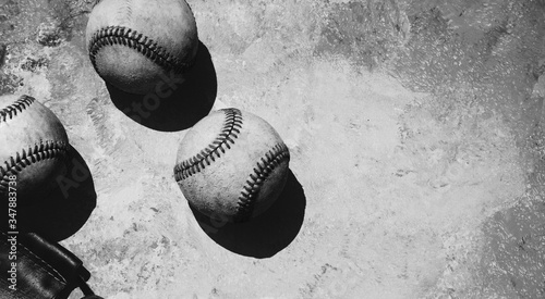 Group of old baseballs in harsh summer sunlight in black and white, copy space on grunge texture background for sport.