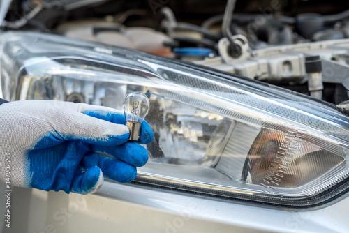 Fototapeta male's hand holding light bulb of car headlight for repair auto obraz
