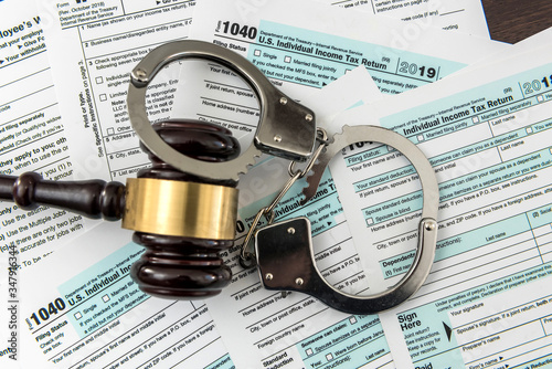 Photo Law concept, 1040 finance tax form with gavel and handcuff