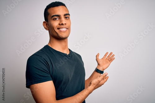 Fotomural Young handsome african american man wearing casual t-shirt standing over white b