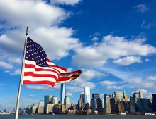 Low Angle View Of American Flag By River Against Blue Sky