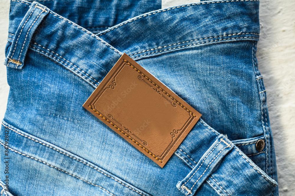 Fototapeta Etykieta skórzana, odzieżowa, zbliżenie spodni jeansowych.