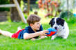 canvas print picture - Active kid boy playing with family dog in garden. Laughing school child having fun with dog, with running and playing with ball. Happy family outdoors. Friendship between animal and kids