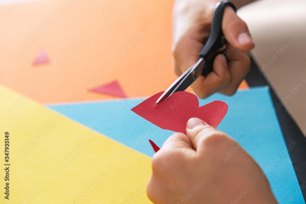 Fototapeta Paper crafts for kids. Child hands cutting colored paper with scissors at the table
