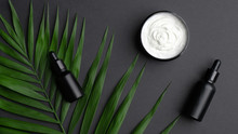 Flat Lay Composition With Black Aromatic Oil Bottles, Body Cream And Palm Leaves On Black Background. SPA Natural Organic Beauty Products, Skincare Concept