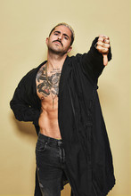 Young Provocative Male In Black Coat Over Naked Tattooed Torso Showing Thumbs Down Gesture In Disapproval While Standing Against Beige Background
