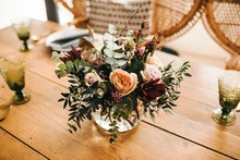 From Above Bouquet Of Miscellaneous Flowers And Green Plant Twigs In Vase With Water On A Wooden Table Set For A Meal With Beautiful Designed Rattan Chair On The Background