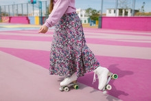 Stylish Young Woman On Roller Skates Posing On Playground