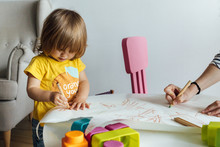 Cropped Unrecognizable Adult Hand Helping Cute Little Girl In Yellow Shirt Sitting At Table Drawing With Colorful Pencils While Spending Time In Playroom In Kindergarten