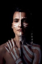 Portrait Of Naked Tender Beautiful Brunette Native American Woman With White Striped Painted On Body Covering Breast Standing In Dark On Black Background Looking At Camera