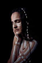 Side View Portrait Of Naked Tender Beautiful Brunette Native American Woman With White Striped Painted On Body Covering Breast Standing In Dark On Black Background With Closed Eyes