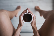 From Above Top View Of Cropped Unrecognizable Woman Legs Holding Cup Of Black Coffee At Home