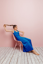 Side View Of Young Woman In Blue Dress Barefoot Looking At Camera Holding Ponytail While Sitting In Chair And Looking Away On Minimalist Pink Background
