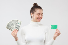 Young Woman In White Turtleneck, Choosing Between Using Dollars In Cash Or Money On Credit Card, Isolated On Gray Background