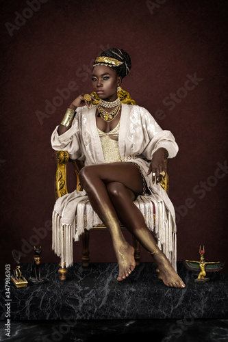 Obraz na plátně A gorgeous young female Egyptian Pharaoh wearing elegant clothing, a gold crown and jewelry is sitting on her golden throne