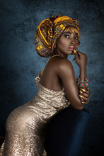 A Gorgeous Young Black Female With Blond Hair Wearing A Beautiful Head Scarf, Golden Sleeveless Dress And Glamorous Jewelry Is Leaning On A Chair.