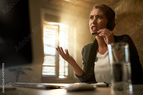 Obraz Below view of frustrated businesswoman having a video conference in the office. - fototapety do salonu