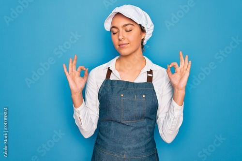 Papel de parede Young beautiful blonde baker woman with blue eyes cooking wearing apron and cap relax and smiling with eyes closed doing meditation gesture with fingers