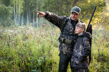 Father Teaching His Son About Gun Safety And Proper Use On Hunting In Nature.