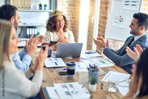 Fototapety, obrazy: Group of business workers smiling happy and confident. Working together with smile on face applauding one of them wearing king crown at the office