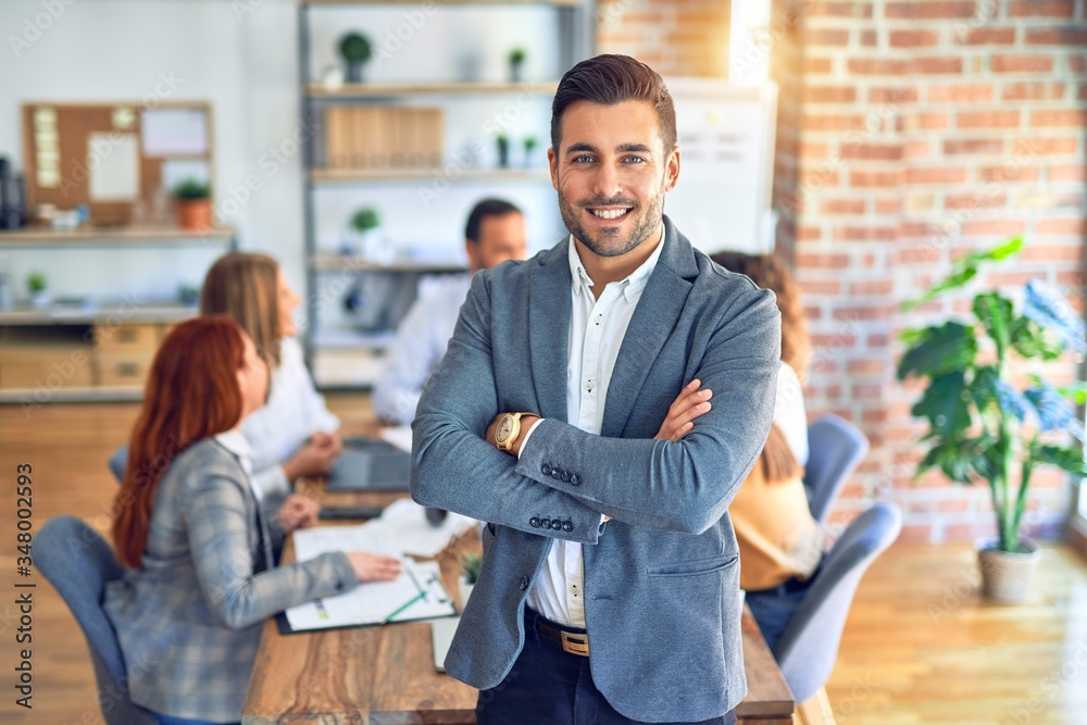 Fototapeta Group of business workers working together. Young handsome businessman standing smiling happy looking at the camera at the office