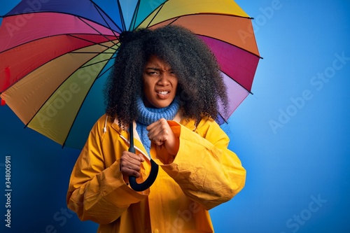 Young african american woman with afro hair under colorful umbrella wearing wint Wallpaper Mural
