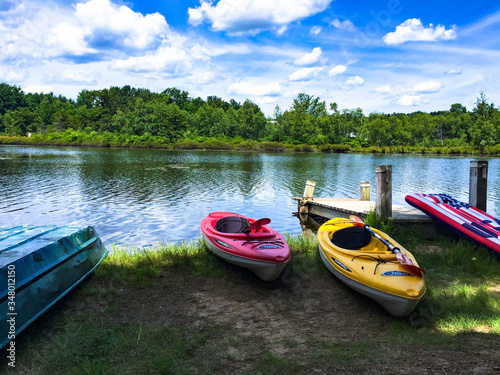 Photo Canoes Moored By Lake Against Cloudy Sky