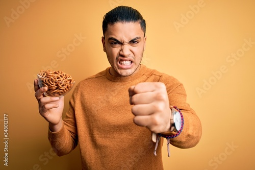 Photo Young brazilian man holding bowl with german salty baked pretzels over yellow ba
