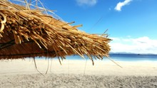 Thatched Roof Parasol At Beach Against Sky