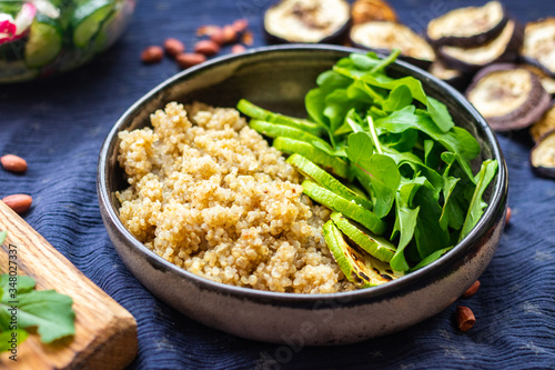 Quinoa amaranth grain cereal cooked porridge with zucchini vegetables and rucola leaves in bowl Wallpaper Mural