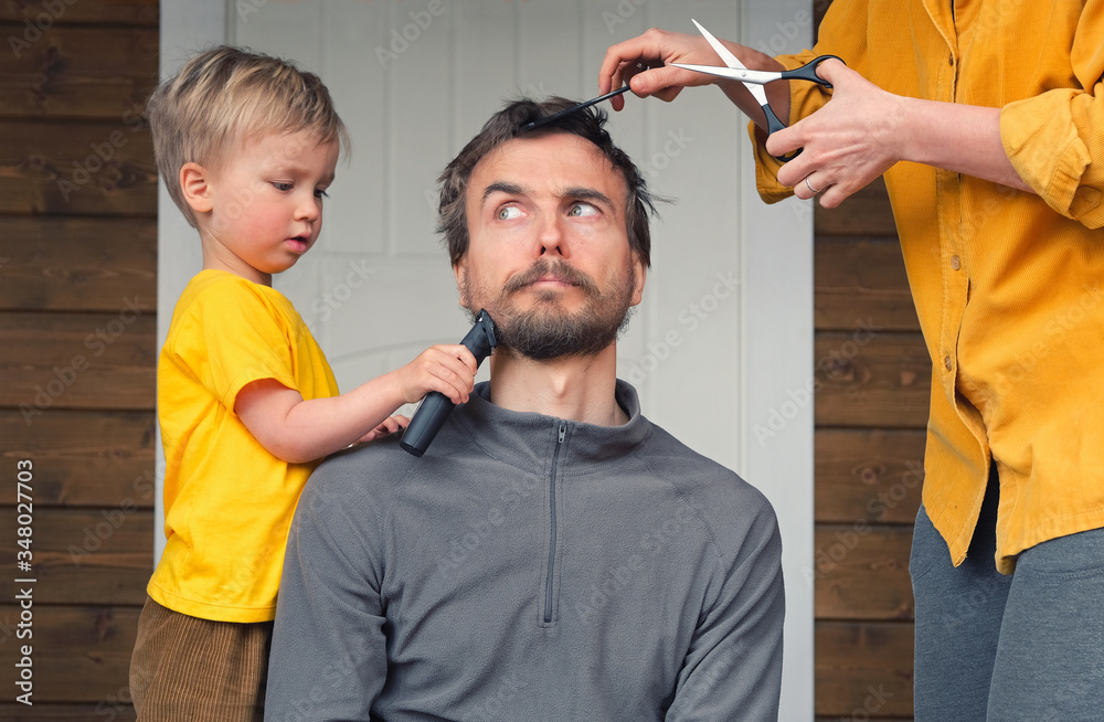 Fototapeta Family haircut at home during quarantine lockdown when closed all hairdressers. Mother cutting hair to father and little child boy cut dad beard with clipper. Beauty and selfcare at home lifestyle.