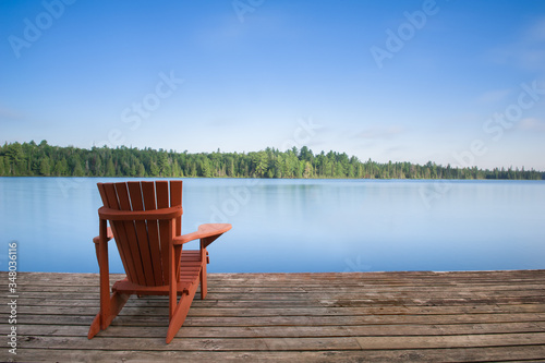 Fotografie, Tablou Adirondack chair sitting on a wood dock facing a calm lake