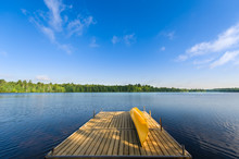 Yellow Canoe Sitting On A Lake Wooden Dock On A Sunny Summer Morning At The Cottage.