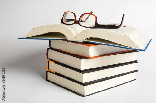 Stacks of hardback books with reading glasses Slika na platnu