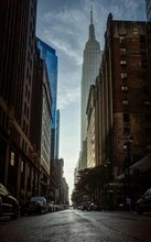 City Street By Empire State Building Against Sky