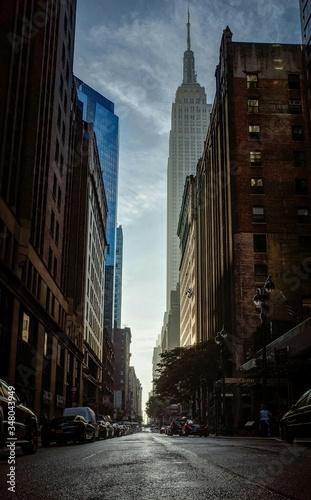 Slika na platnu City Street By Empire State Building Against Sky