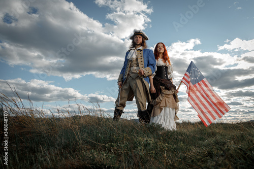 Foto Man in form of officer of War of Independence and girl in historical dress of 18th century